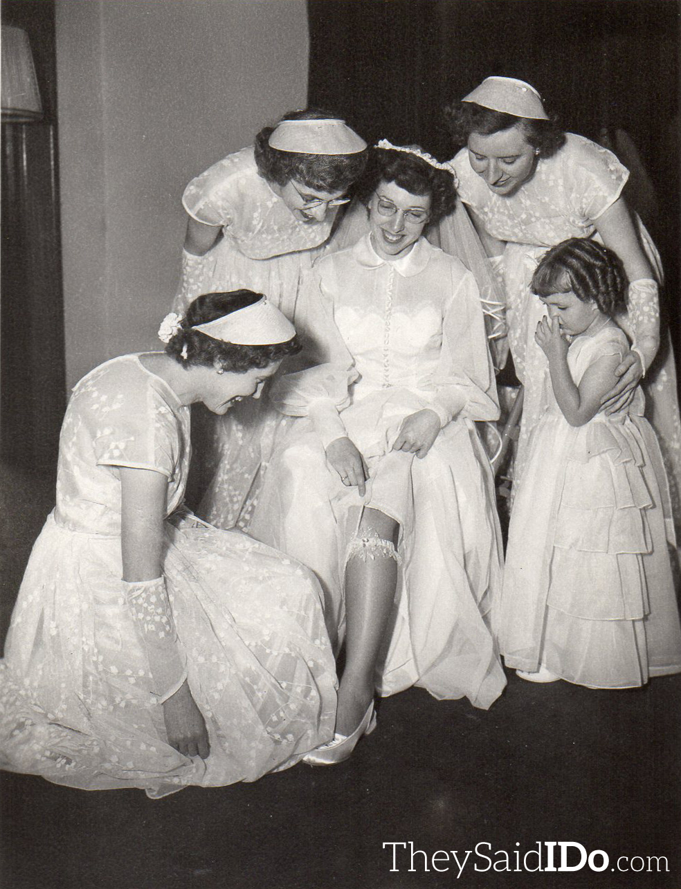 The bridesmaids look on as the bride shows off her garter Lansing, MI 1951 {TheySaidIDo.com}